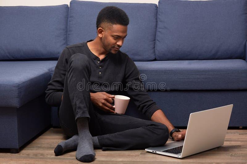 Tiro interno do homem deleitado considerável que senta-se perto do sofá em casa, passando seus fins de semana com portátil, rede  fotografia de stock royalty free