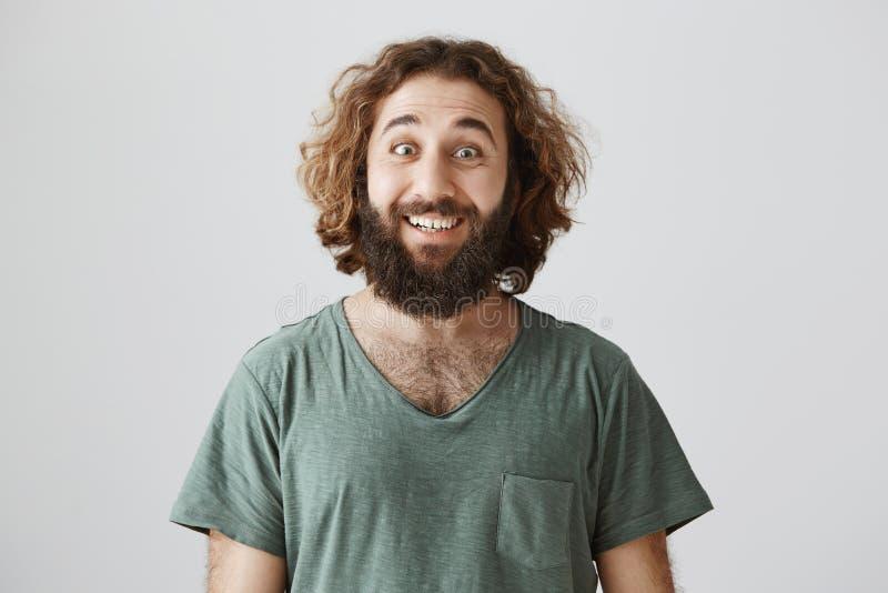 Tiro interno do homem oriental bonito com atitude otimista que sorri amplamente e que olha na câmera com olhos alargados fotos de stock