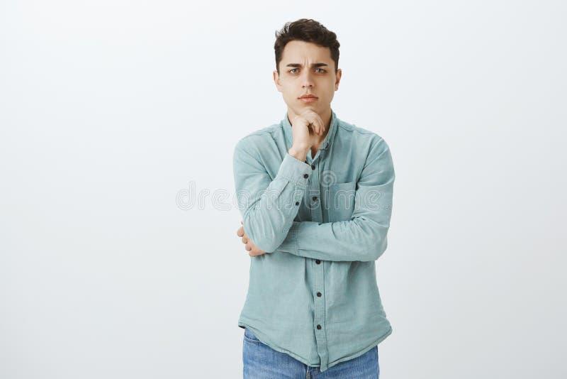 Tiro interno do indivíduo incomodado focalizado esperto com cabelo preto curto no equipamento ocasional, guardando a mão no queix foto de stock royalty free