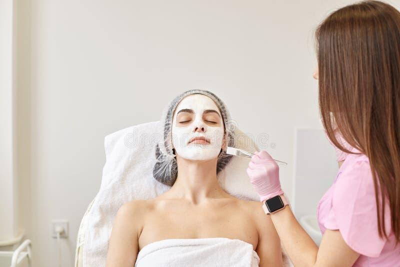 Tiro interno na sala de estar de beleza do cliente e do esteticista com creme aplicado dos termas da escova profissional na cara  imagens de stock