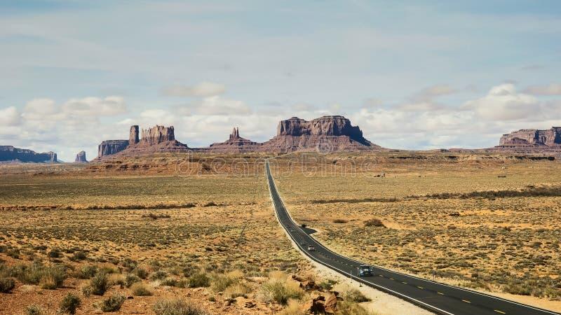 Tiro largo de la exposición de los coches que viajan a lo largo de la carretera 163 en el valle del monumento en Utah fotos de archivo