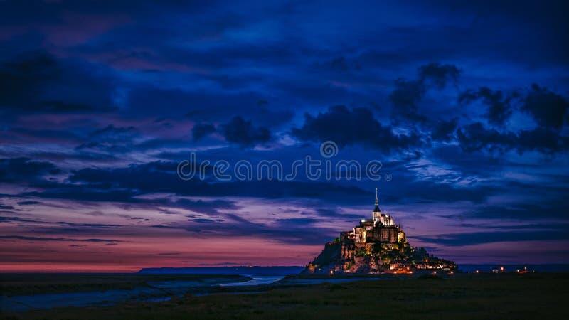 Tiro largo de um castelo iluminado na distância com surpresa de nuvens azuis no céu foto de stock royalty free