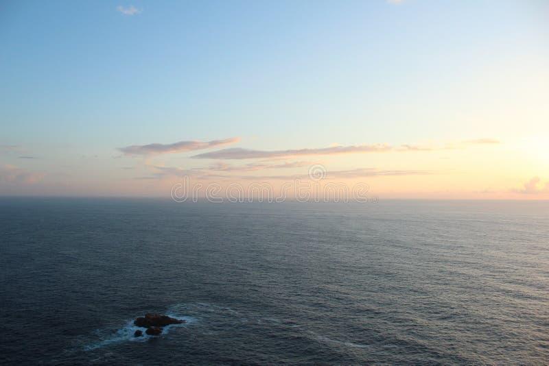 Tiro largo do oceano bonito com surpresa do céu azul e das nuvens durante o nascer do sol fotos de stock