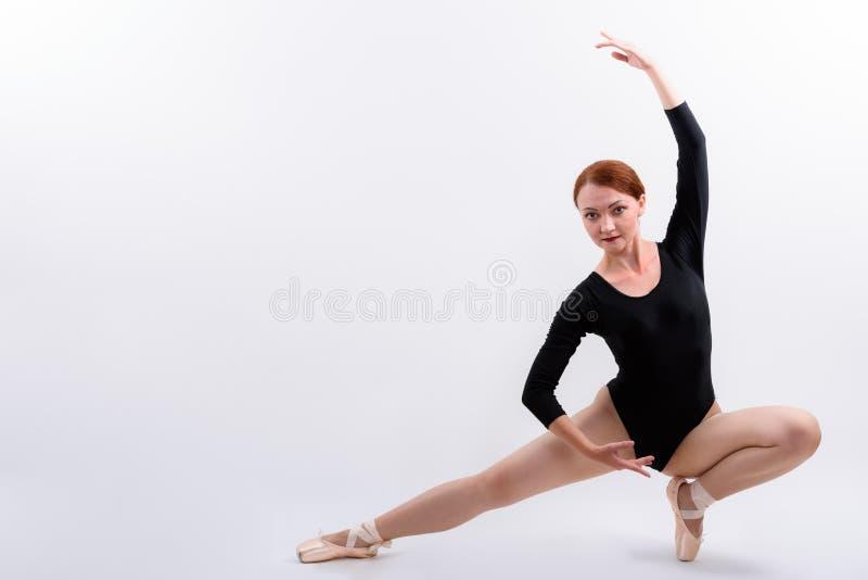 Tiro lleno del cuerpo del bailarín de ballet de la mujer que presenta abajo en el piso imagen de archivo libre de regalías