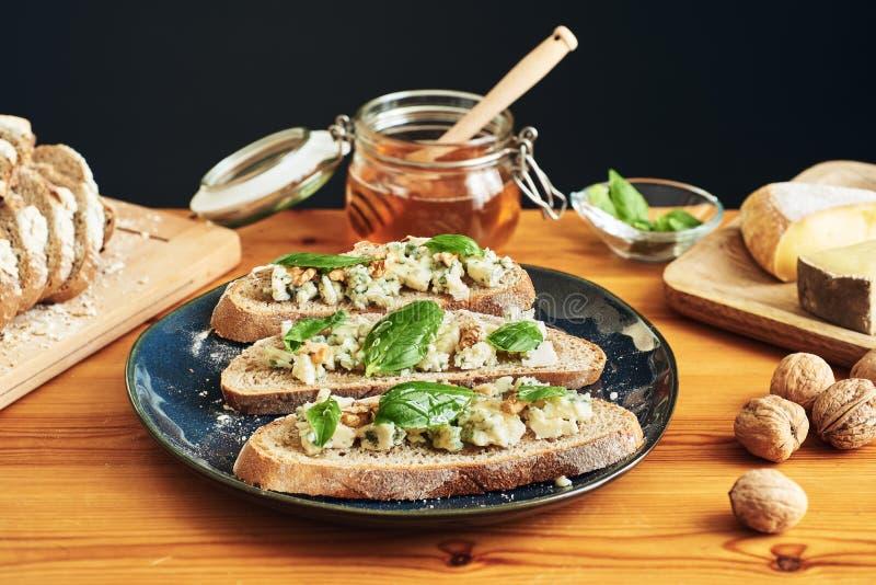 Tiro lleno y foco que apilan en una placa de tostadas con queso, las nueces, la miel y la albahaca del Roquefort imágenes de archivo libres de regalías