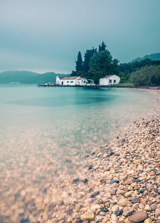 Tiro longo bonito da exposição do oceano com uma casa branca tradicional no fundo Corfu Greece imagens de stock