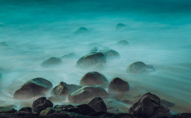 Tiro longo da exposição das ondas de oceano que batem as rochas pela praia fotografia de stock royalty free