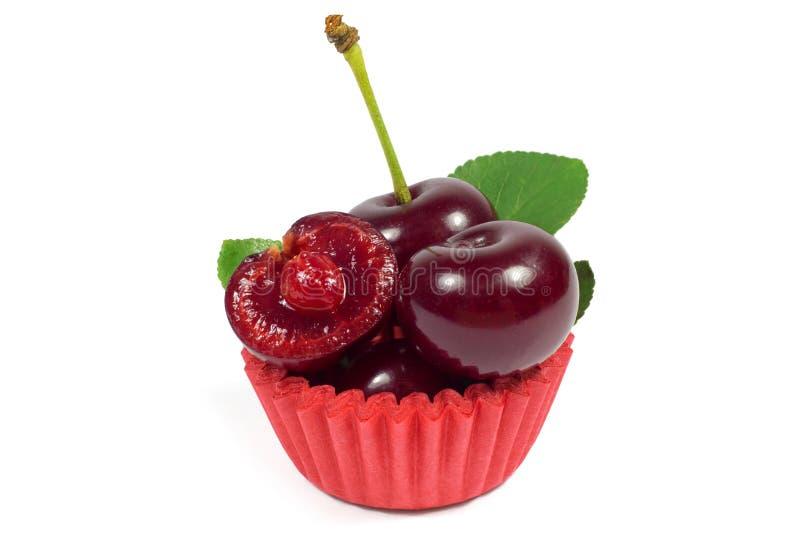 Tiro macro da cereja suculenta com a folha no envoltório vermelho do queque isolado no branco fotos de stock