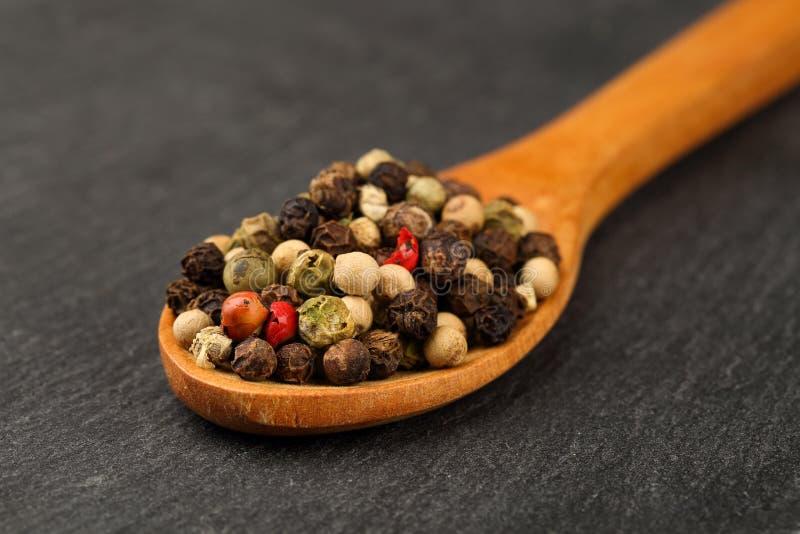 Tiro macro de la mezcla negra, verde, blanca y roja del grano de pimienta en una cuchara de madera en un tablero de piedra oscuro imagen de archivo
