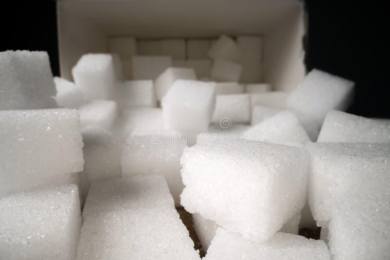 Tiro macro de los cubos del azúcar al lado de la caja del cartón en la tabla de madera Edulcorante malsano de la comida, cubos  foto de archivo