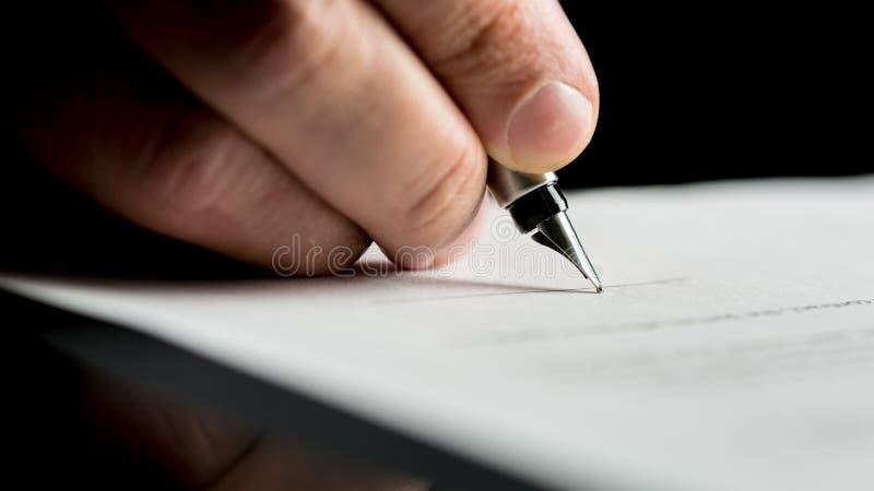 Tiro macro de uma mão de um homem de negócios que assina ou que escreve um docum imagem de stock royalty free