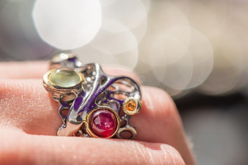 Tiro macro del anillo de compromiso de plata en fondo colorido, chispeante imágenes de archivo libres de regalías