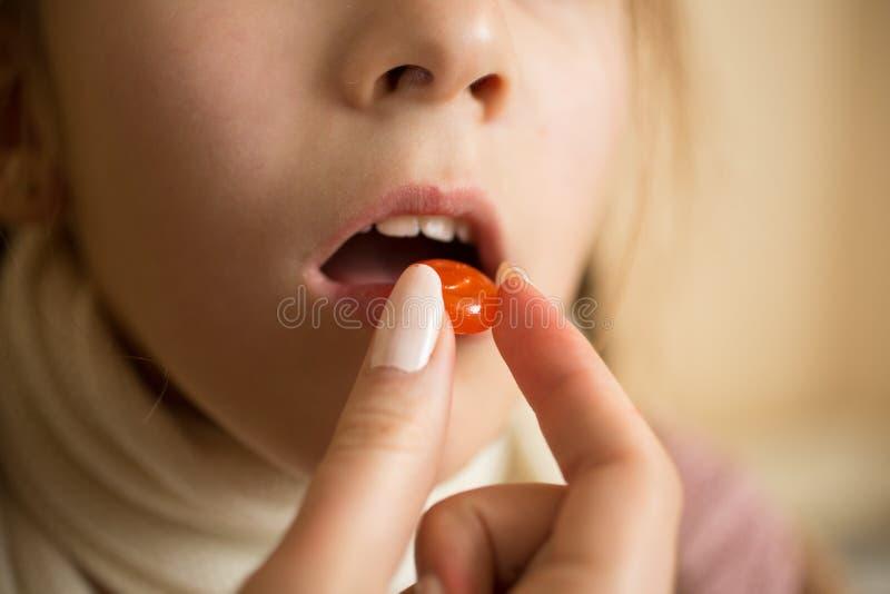 Tiro macro del pequeño enfermo con la muchacha de la gripe que toma la píldora en boca imagen de archivo