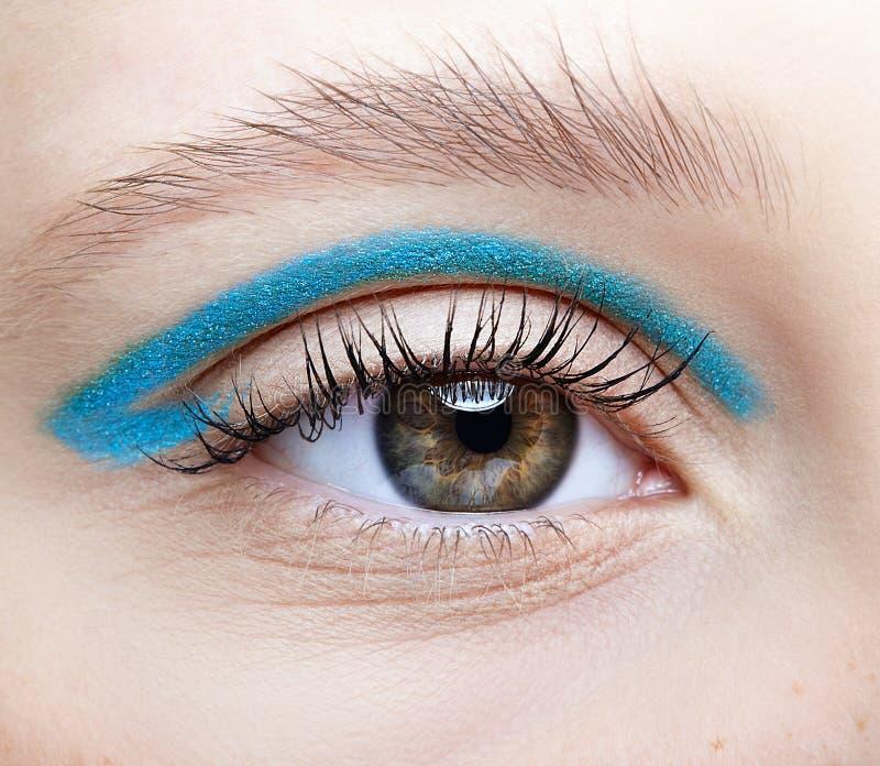 Tiro macro do close up do olho fêmea humano e com sombras de olhos fumarentos azuis foto de stock royalty free