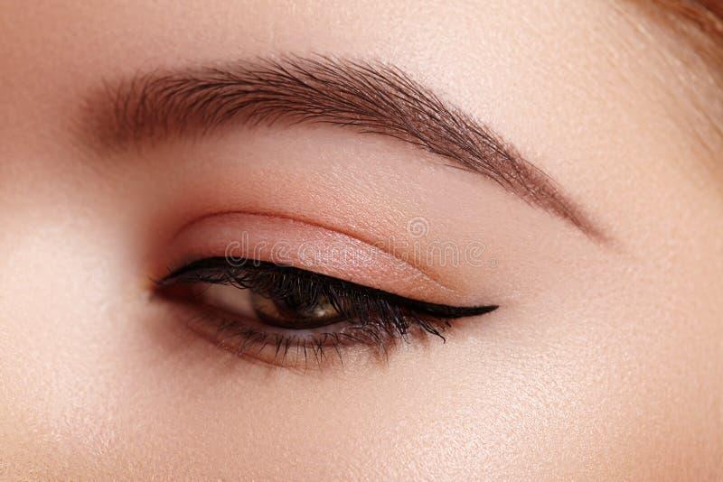 Tiro macro hermoso del ojo femenino con maquillaje cl?sico del l?piz de ojos Forma perfecta de cejas Cosm?ticos y maquillaje fotografía de archivo libre de regalías