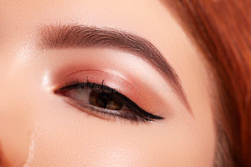 Tiro macro hermoso del ojo femenino con maquillaje cl?sico del l?piz de ojos Forma perfecta de cejas Cosm?ticos y maquillaje fotografía de archivo