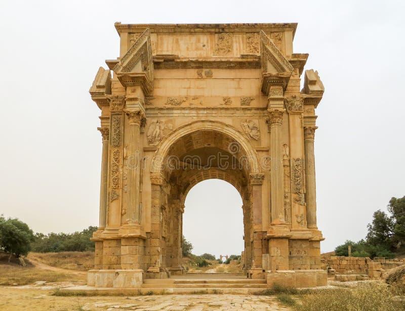 Tiro medio del arco icónico de Septimius Severus en las ruinas romanas antiguas de Leptis Magna en Libia imágenes de archivo libres de regalías