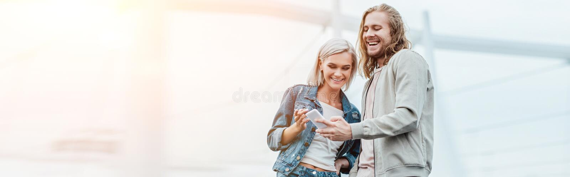 tiro panorámico de pares jovenes felices usando smartphone junto foto de archivo libre de regalías