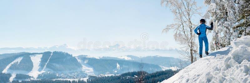 Tiro panorámico de un esquiador de sexo femenino que descansa encima de la montaña observando la naturaleza en la estación de esq imagen de archivo