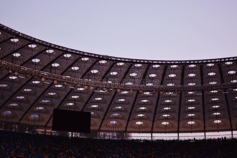 Tiro parcial de um estádio que indica o telhado, as fileiras de assentamento superiores e as cadeiras de um grande monitor fotos de stock