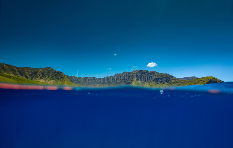 Tiro partido del agua azul y de las montañas verdes fotos de archivo