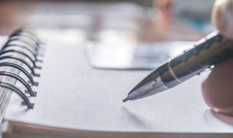 Tiro próximo de uma pena que escreve algo no documento do enchimento do papel do formulário de candidatura - assinando um contrat imagens de stock royalty free