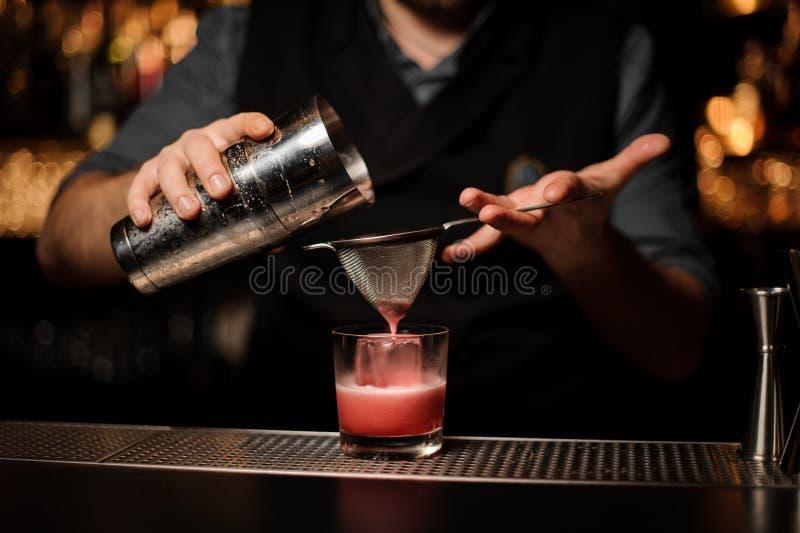 Tiro próximo do barman que faz o cocktail com abanador e peneira imagem de stock