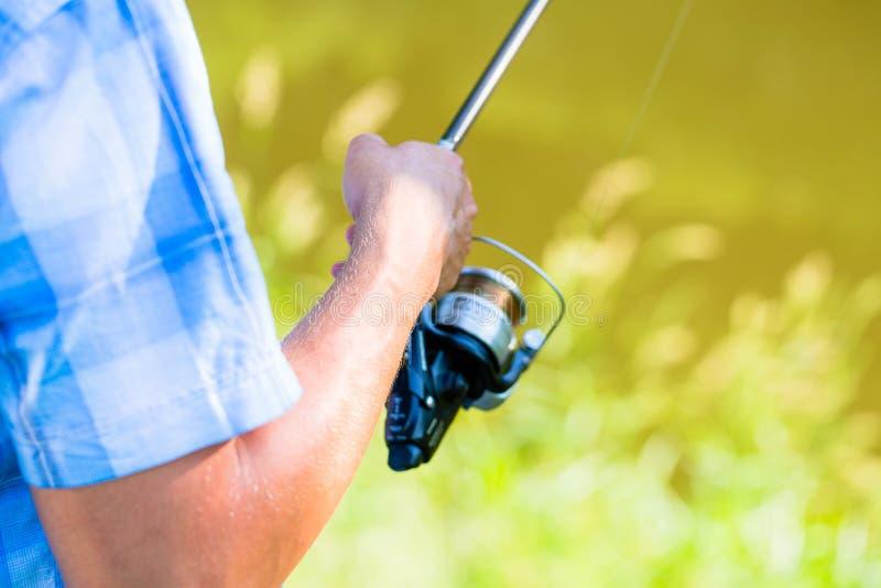 Tiro próximo do pescador do esporte que bobina na linha na vara de pesca imagem de stock
