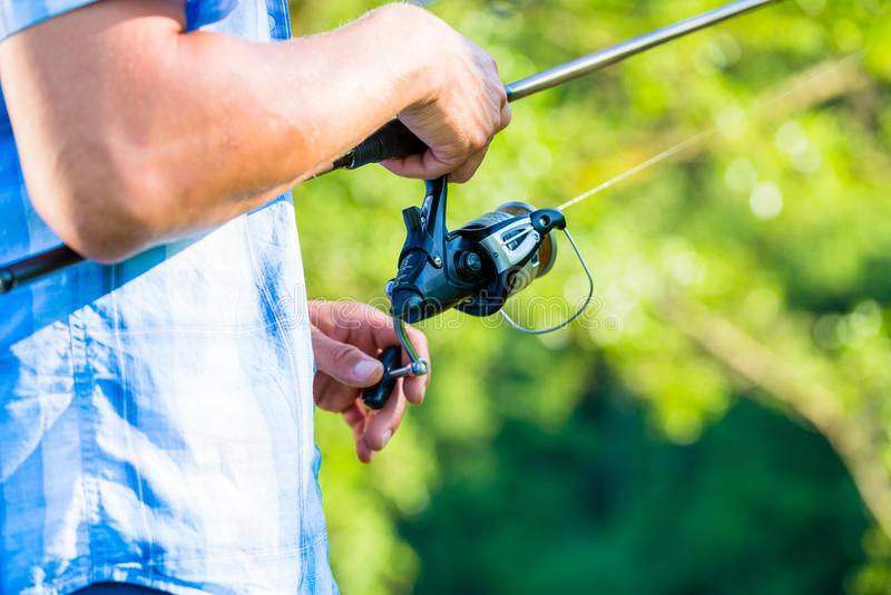 Tiro próximo do pescador do esporte que bobina na linha na vara de pesca fotos de stock