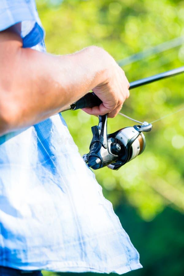Tiro próximo do pescador do esporte que bobina na linha na vara de pesca foto de stock
