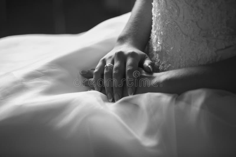 Tiro preto e branco da noiva que guarda as mãos no vestido de casamento fotos de stock royalty free