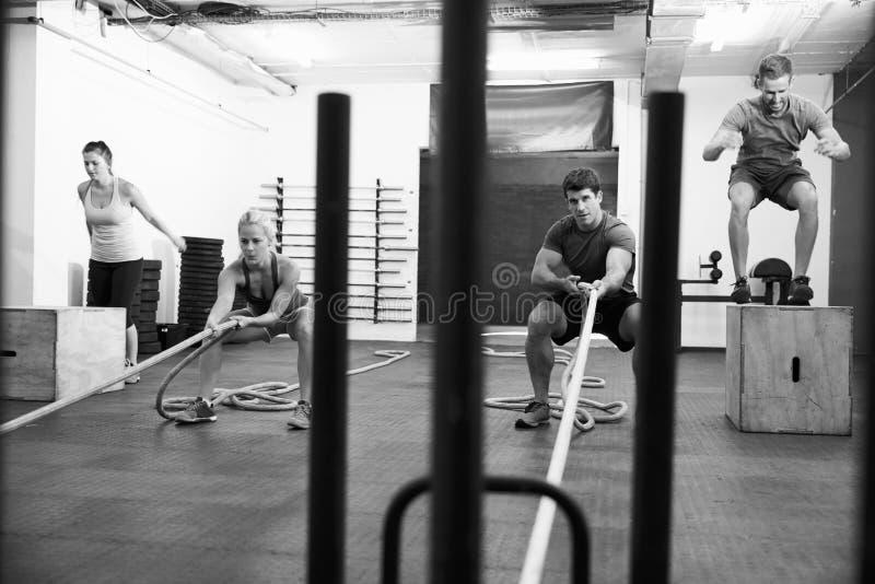 Tiro preto e branco dos povos no treinamento do circuito do Gym imagens de stock