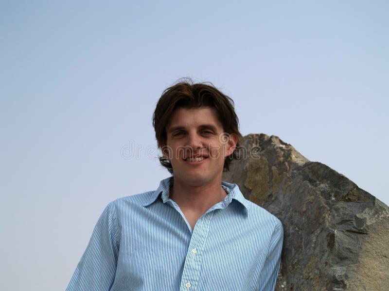Tiro principal del retrato de un hombre twentysome hermoso con los ojos azules contra una pared roja con las líneas negras imágenes de archivo libres de regalías