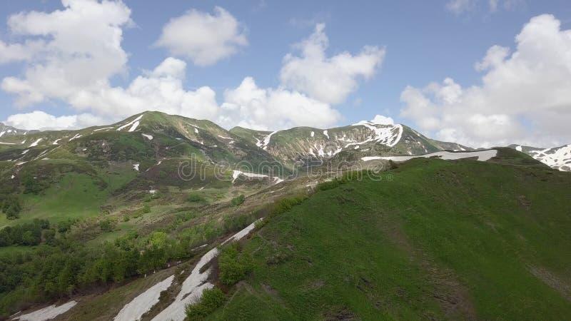 Tiro a?reo das partes superiores de montanhas verdes com os pontos pequenos da neve imagens de stock royalty free