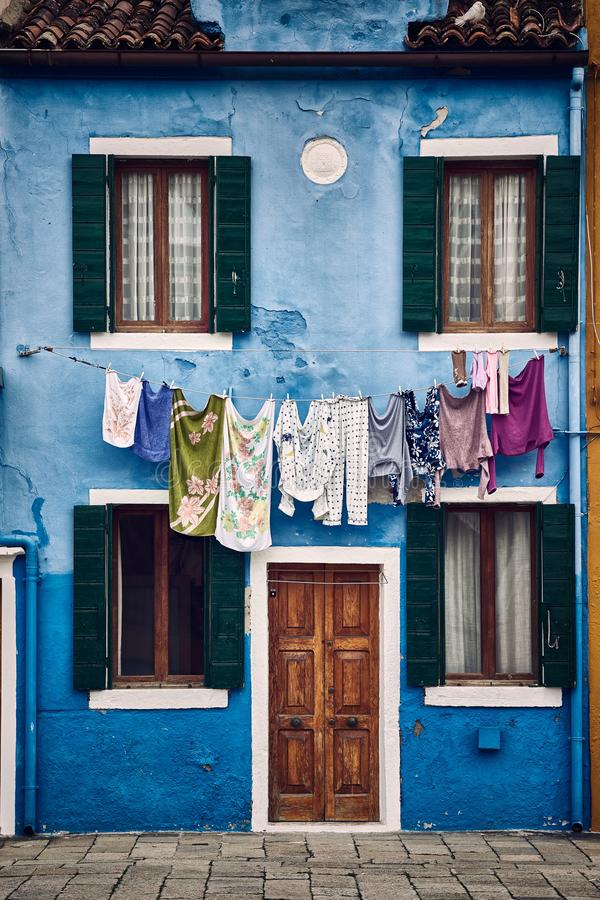Tiro simétrico vertical hermoso de un edificio azul suburbano con la ropa que cuelga en una cuerda imagen de archivo libre de regalías