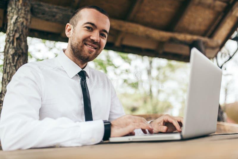 Tiro sincero del hombre joven feliz del freelancer que se sienta en el café al aire libre con la PC genérica del ordenador portát foto de archivo