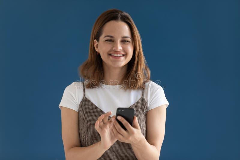Tiro sonriente del estudio de la nueva aplicación de la transferencia directa del smartphone de la tenencia de la mujer fotografía de archivo libre de regalías