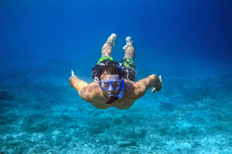 Tiro subaquático de um homem novo que mergulha em um mar tropical fotos de stock royalty free