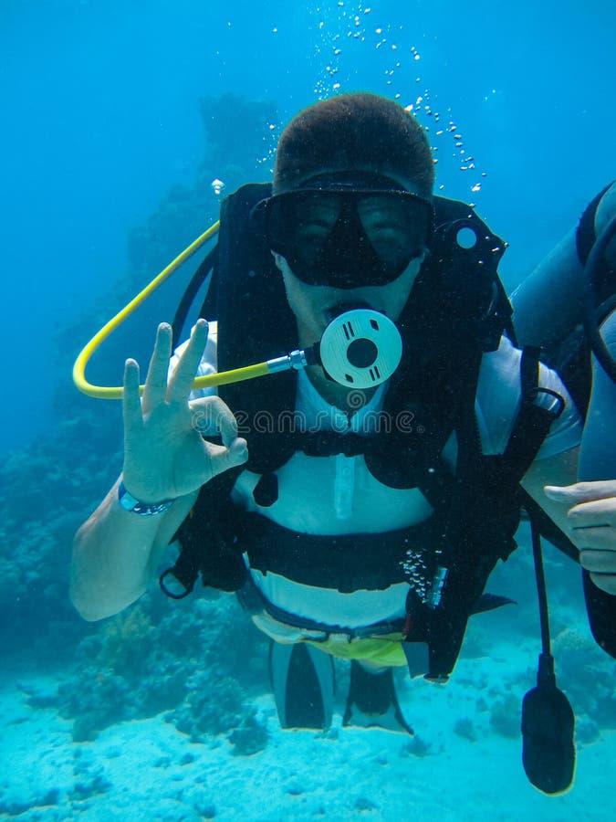 Tiro subaquático de um mergulho do homem que mostra o sinal aprovado fotografia de stock royalty free