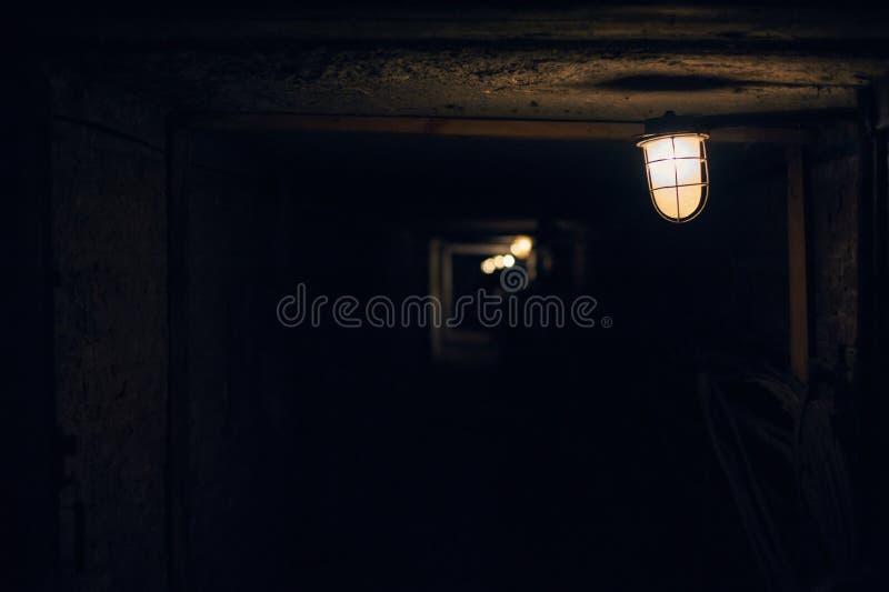 Tiro subterráneo largo del ángulo del túnel del ladrillo Linterna vieja en el primero plano fotografía de archivo
