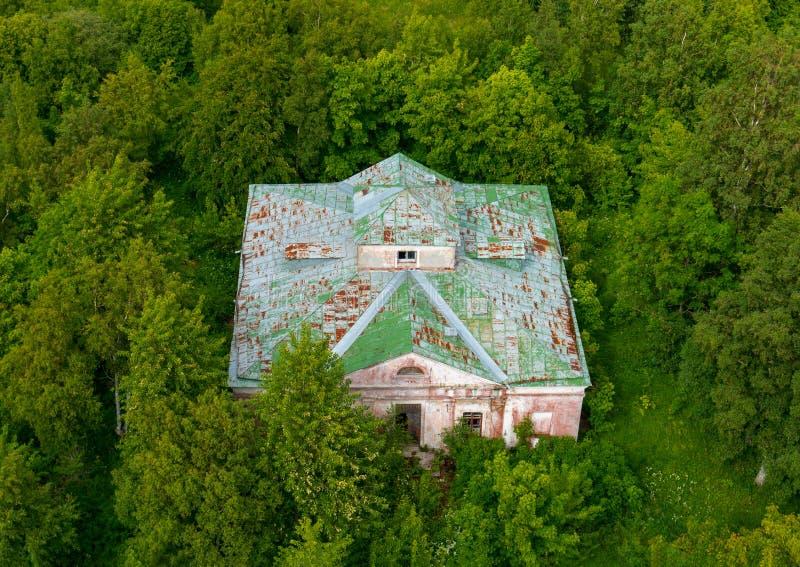 Tiro superior da vista aérea da construção abandonada na floresta verde densa intransitável imagens de stock