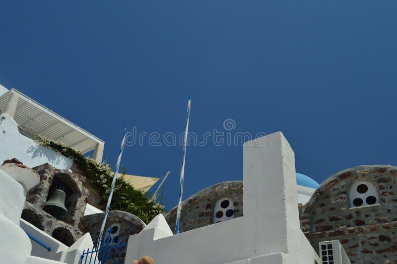 Tiro tajado de una entrada de la iglesia y de su campanario del anexo en la ciudad hermosa de Oia en la isla de Santorini Arquite fotos de archivo libres de regalías