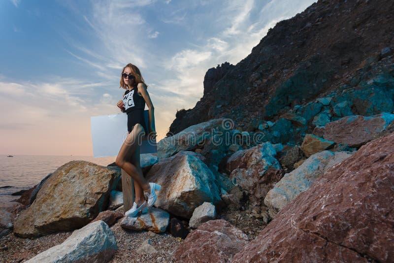 Tiro teenager di modo della ragazza alla spiaggia di tramonto con vuoto fotografia stock