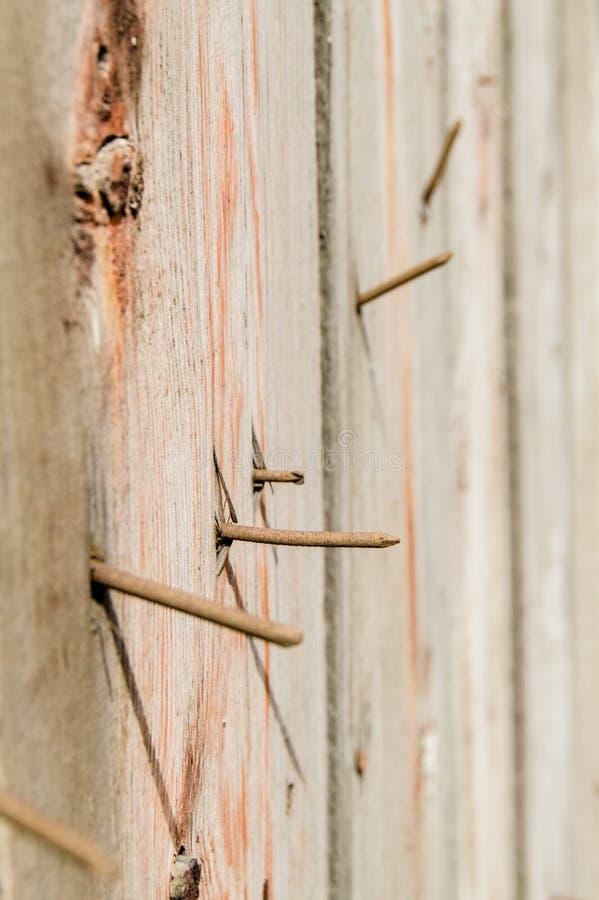 Tiro vertical, close-up dos pregos oxidados velhos que colam fora das placas idosas escuras, textura de madeira, superfície do to fotografia de stock