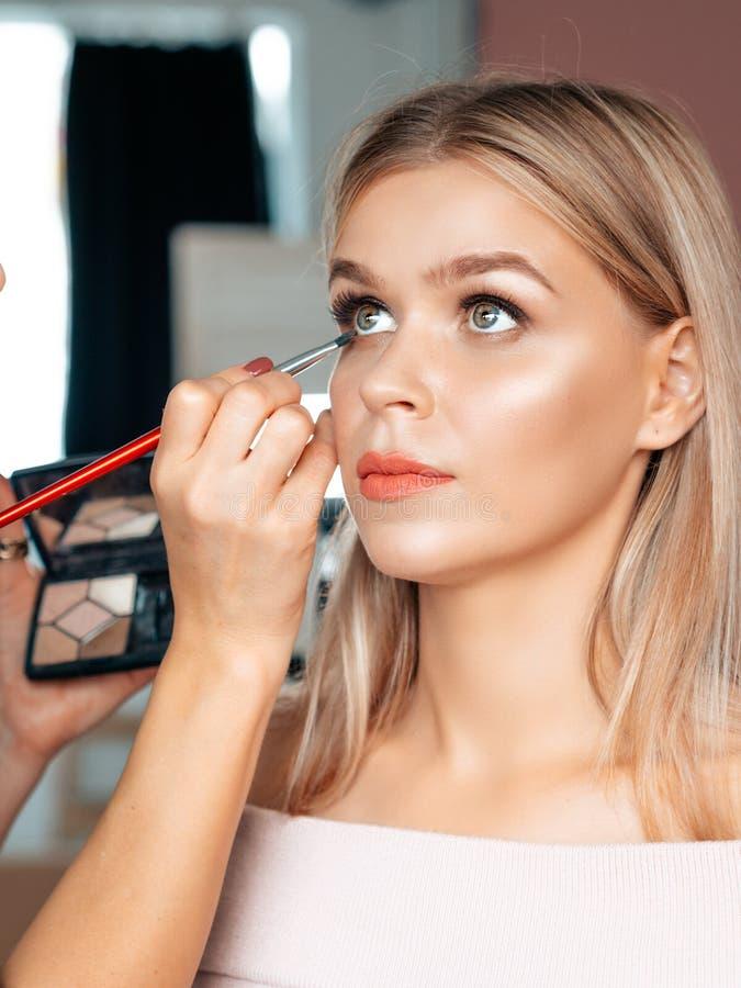 Tiro vertical da TV nos bastidores da maquiagem artista tint eyelashes em uma atriz loira Fechar o retrato facial foto de stock royalty free