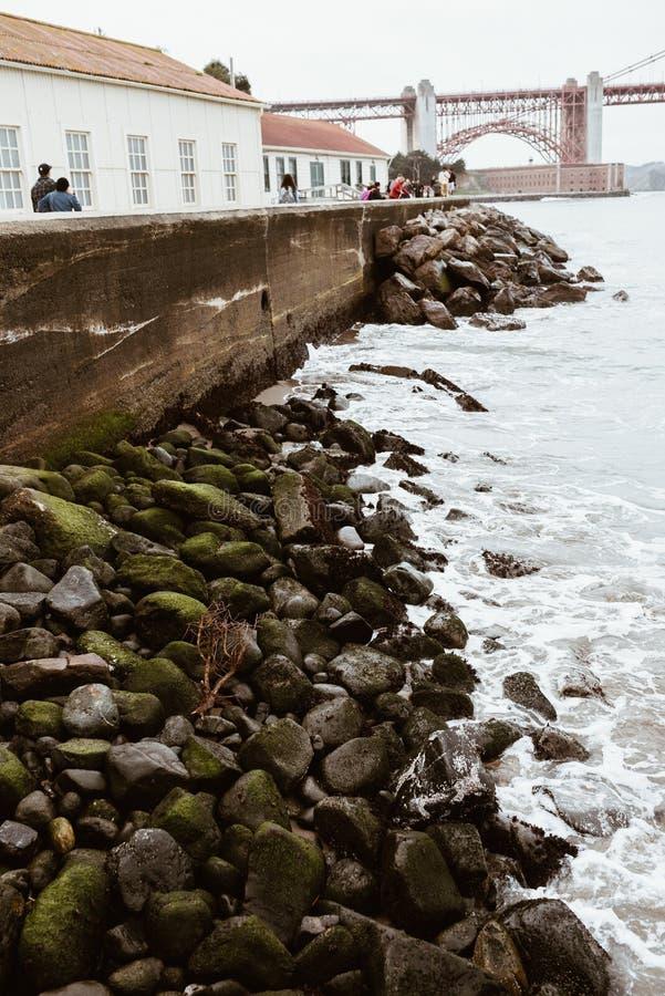 Tiro vertical de la gente que se coloca cerca de las verjas de piedra en la costa del mar en San Francisco, CA fotos de archivo libres de regalías