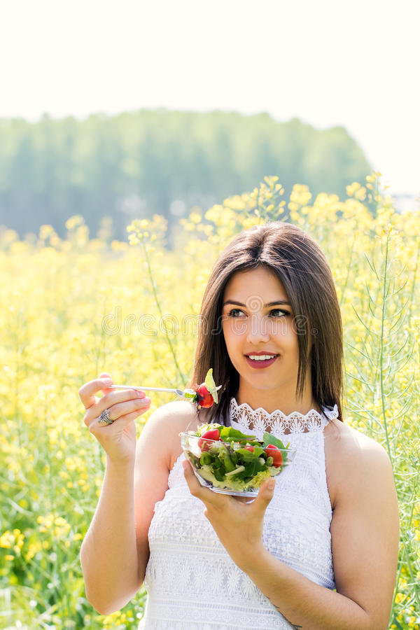 Tiro vertical de la muchacha que come la ensalada en campo de flor imagen de archivo libre de regalías