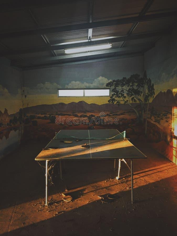 Tiro vertical de la tabla de ping-pong en un cuarto que se retira en una pared y el sol que brillan a través foto de archivo