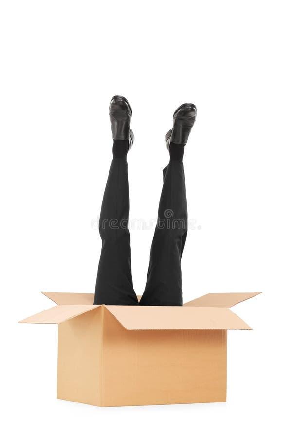 Tiro vertical de las piernas masculinas que se pegan fuera de una caja fotos de archivo libres de regalías