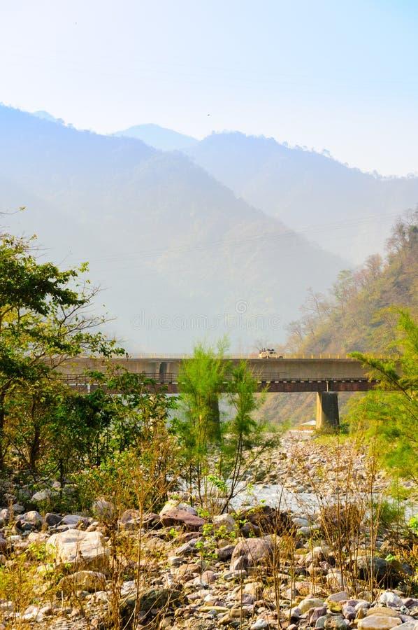 Tiro vertical de montañas, del puente y del cauce del río seco fotografía de archivo